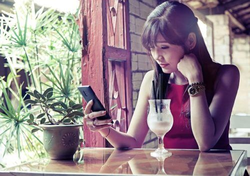 girl-sitting-with-cocktail-looking-at-her-phone